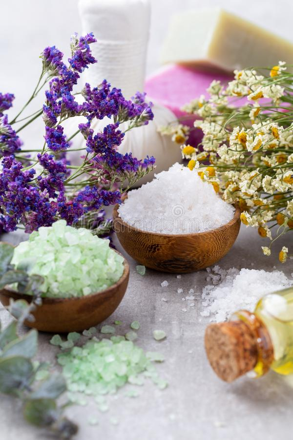 Sea salt in bowl, aroma oil in bottles, Wellness and flowers on grey textured background and flowers on vintage wooden background stock photos