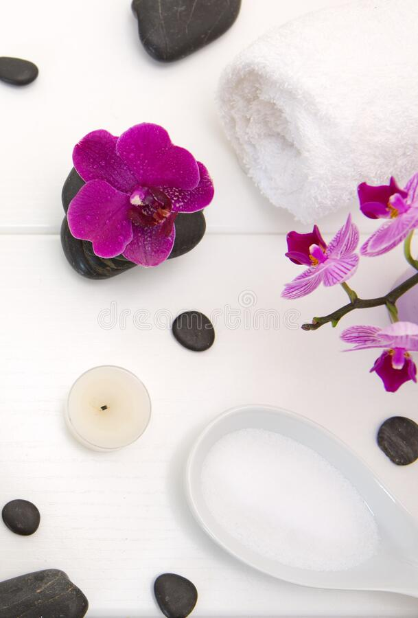 Spa setting with pink orchids, black stones on white wood background. Spa setting with pink orchids, black stones and bath salts on white wood background royalty free stock images