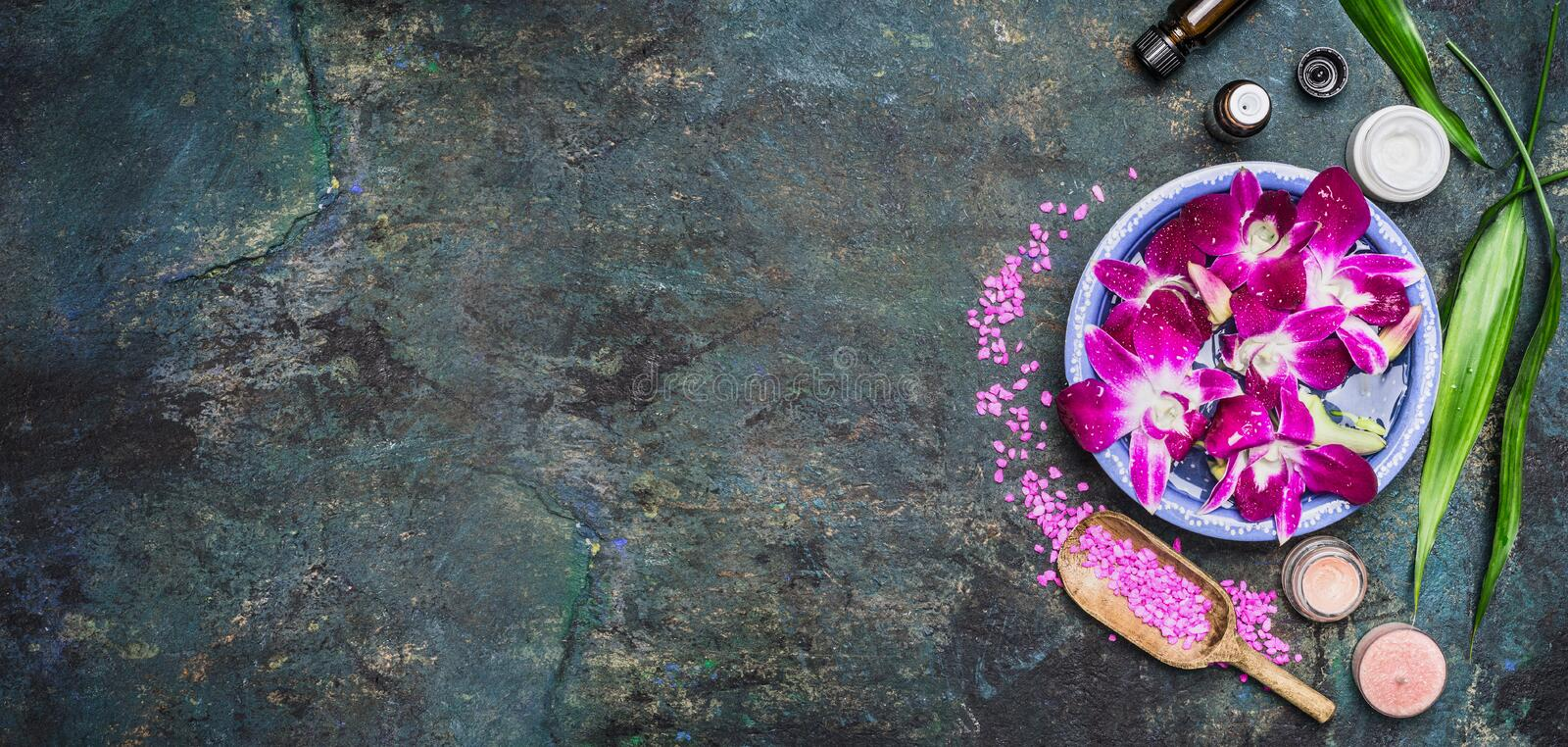 Spa setting with water bowls , pink orchid flowers ,sea salt, cosmetic cream and essential oil on dark rustic background. Top view, place for text, horizontal stock images