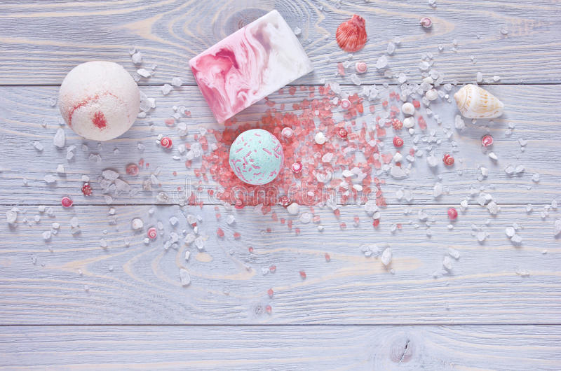 Spa and shower accessories. Bath bombs, aromatherapy salt,handmade soap bar and seashells on wooden background. stock photos