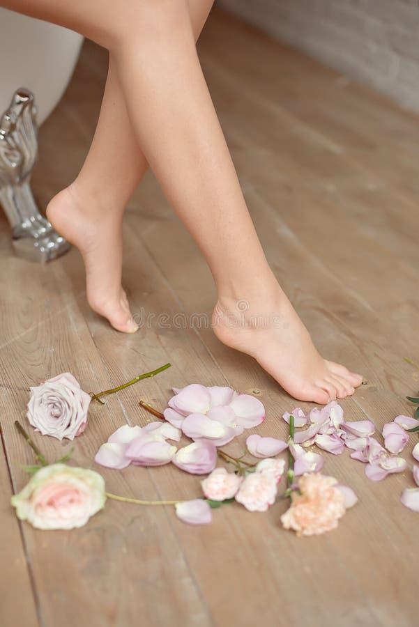Spa, skönhet och wellnessbadrumbegrepp med nya rosa kronblad och blommor spridda runt om bränningstearinljus och royaltyfri foto