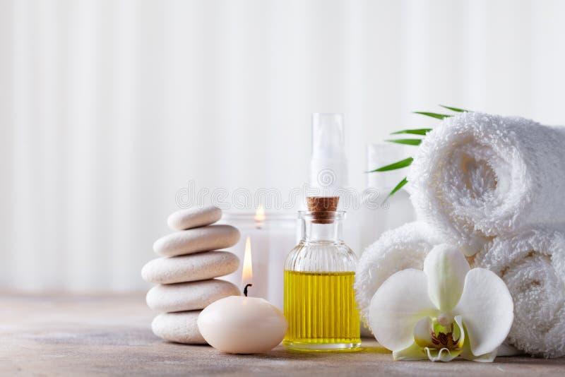 Spa, skönhetbehandling och wellnessbakgrund med massagekiselstenar, orkidéblommor, handdukar, kosmetiska produkter och brinnande  royaltyfria bilder