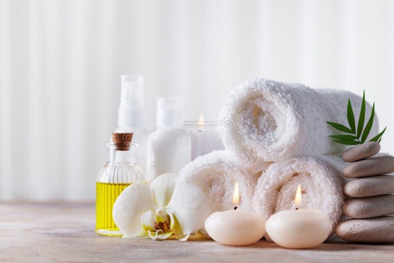 Spa, skönhetbehandling och wellnessbakgrund med massagekiselstenar, orkidéblommor, handdukar, kosmetiska produkter och brinnande  royaltyfri foto
