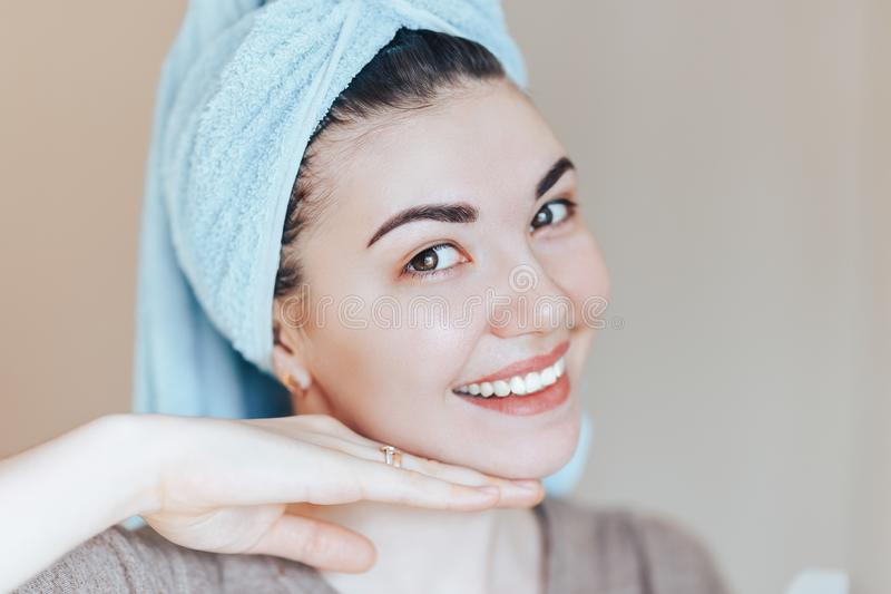 Spa skin care beauty woman wearing hair towel after beauty treatment. Beautiful young woman with perfect skin smiling looking at royalty free stock image