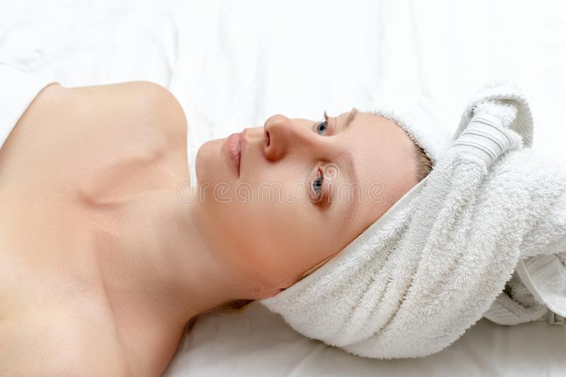 Spa skin care beauty woman wearing wrapped hair towel on a head after beauty treatment, Caucasian woman lying on white sheet royalty free stock photo