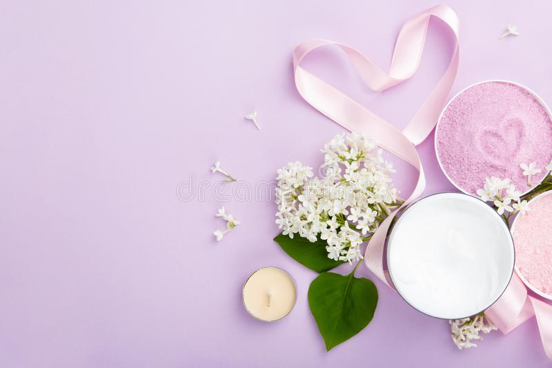 Spa and skin care products cream, and sea bath salt on purple background with spring white lilac blossom. stock photo