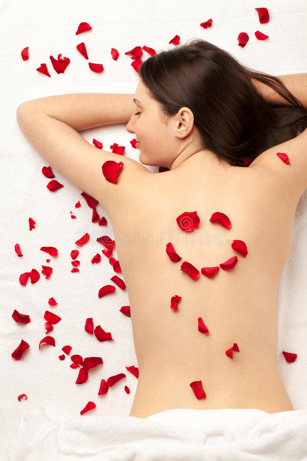 Spa smile. Smiling girl with smiley made of rose petals on back; focus on the face royalty free stock photo
