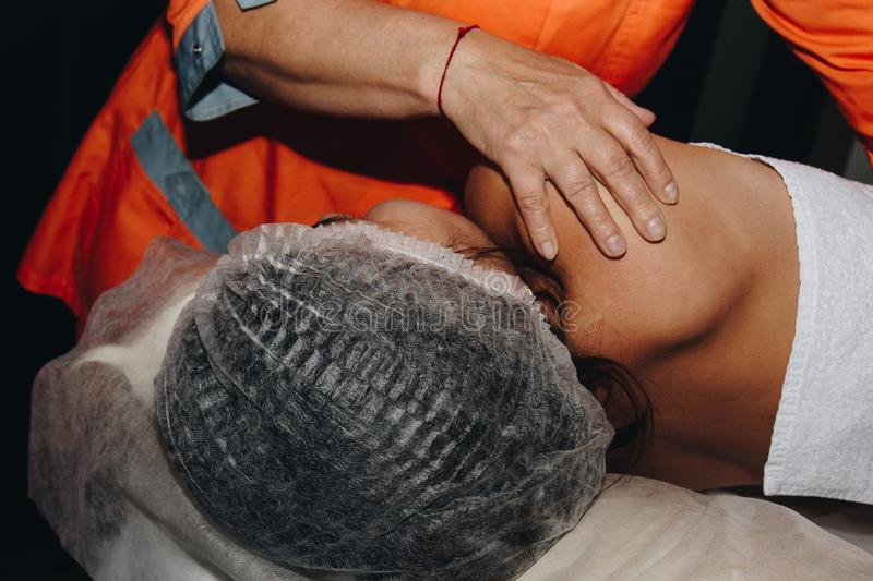 A spa specialist is twisting the spine of a young girl in a medical cap. bodily procedures close-up. recovery from back pain stock photo