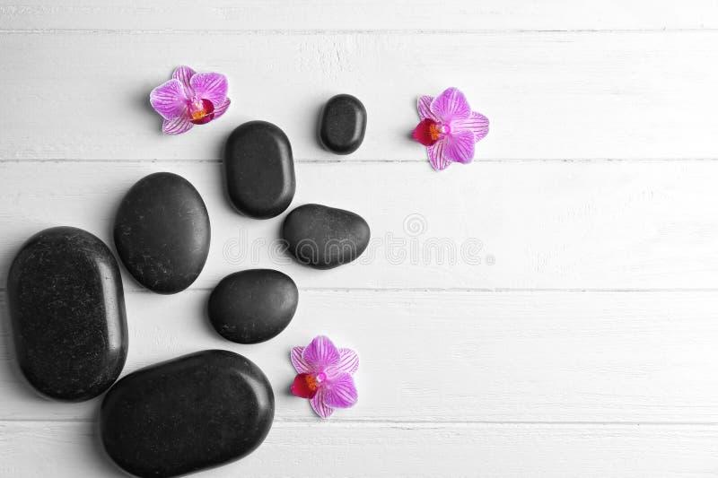 Spa stenar och härliga blommor på vit träbakgrund, bästa sikt arkivfoto