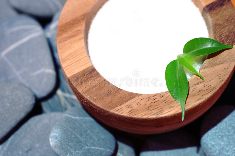 Spa still life. A wooden bowl with spa salt on a layer of rocks