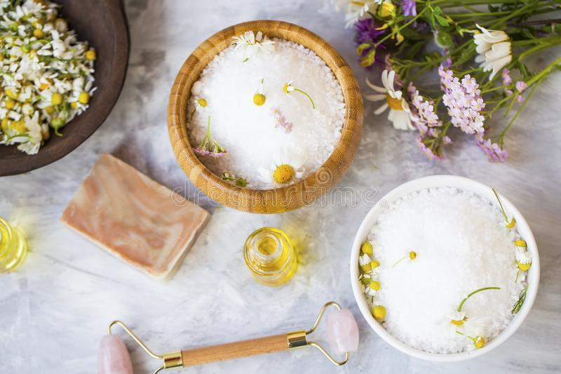 Spa still life bath salts with essential oils and medicinal healing herbs. Flowers and plants stock images
