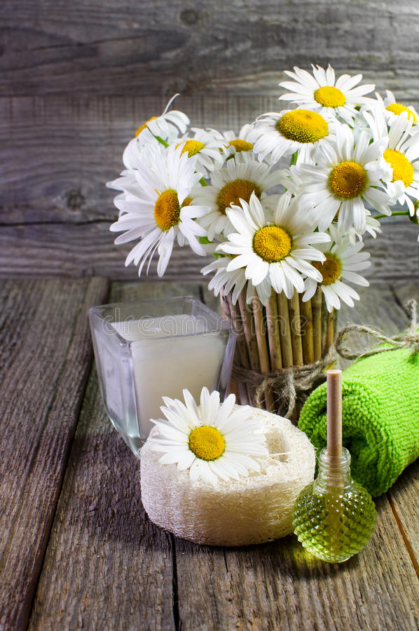 Spa still life. Beautiful daisies, candle and other accessories on wooden surface. stock images