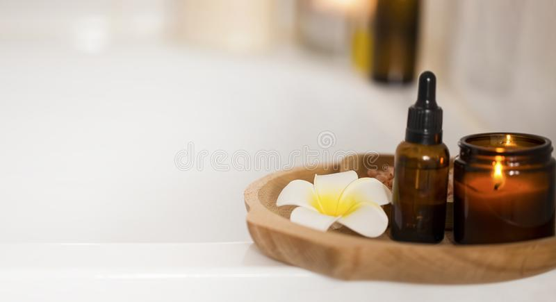 Spa still life with candle, body oil and frangipani flower on wooden plate, home spa and aromatherapy set, clean beauty stock photo