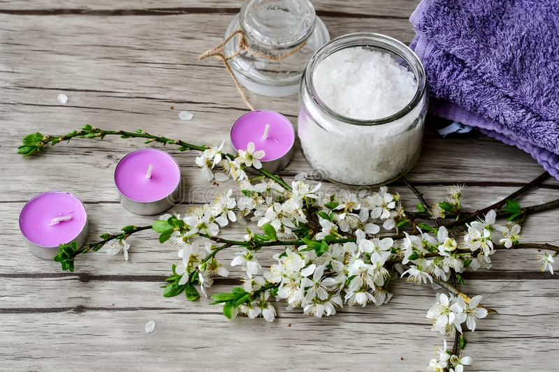 Spring Spa. Spa still life with candles, body scrab ,purple towel and spring bloom royalty free stock photo