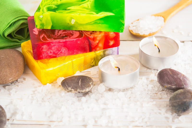 Spa still life with salt, stone and three pieces of soap. With aroma lamp on the white wooden table with copy space royalty free stock photo
