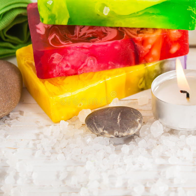 Spa still life with salt, stone and three pieces of soap. On the white wooden background with copy space royalty free stock photo