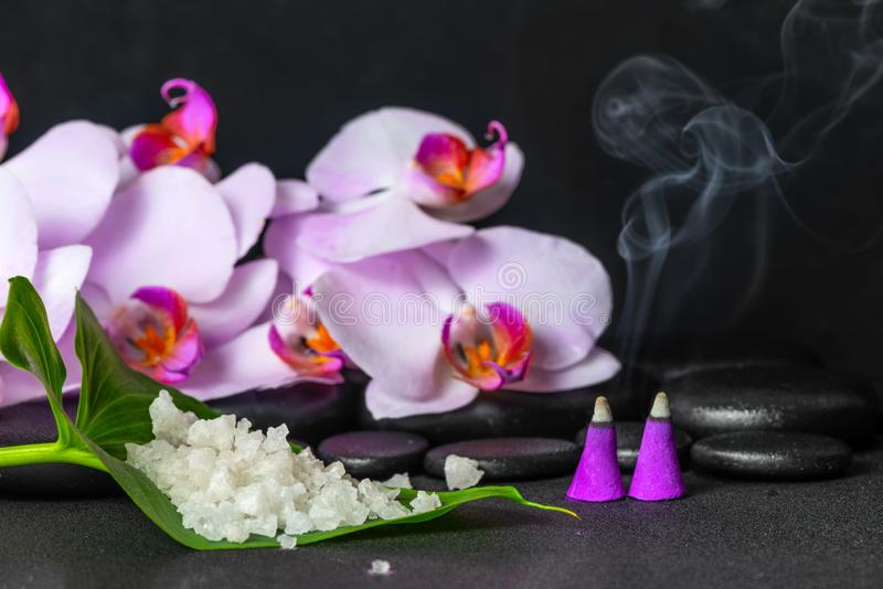 spa still life of sea salt on leaf, lilac orchid with drops and burning aroma incense cones over black zen stones royalty free stock image