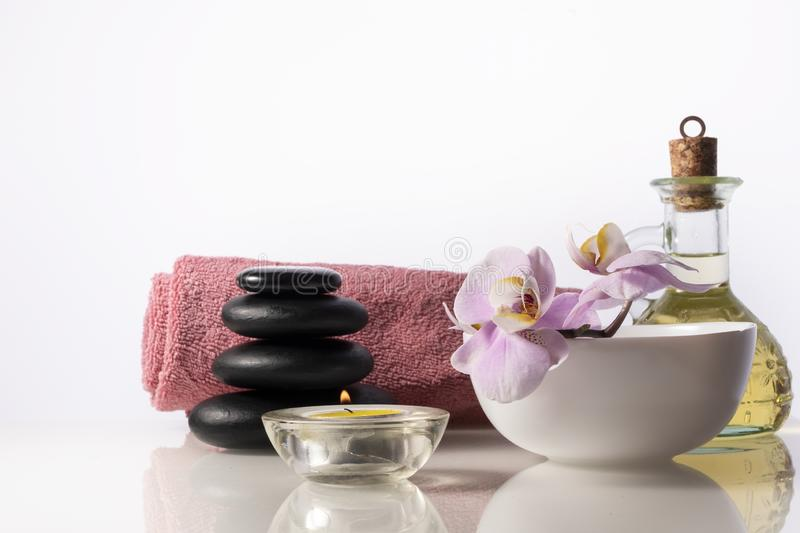 Spa still life with zen stones, orchid flower in bowl, candle, bottle with oil and towel. royalty free stock photos