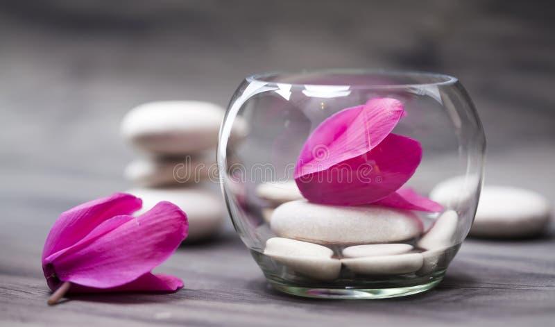 Spa stilleben med den rosa orkidén, den vita zenstenen och testearinljuset arkivbilder