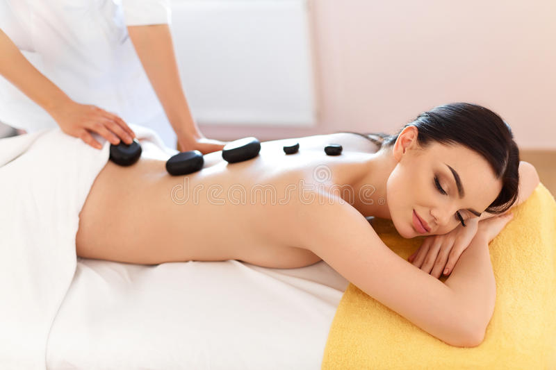 Spa Stone Massage. Young Woman Have Hot Stone Massage Treatments. Spa Hot Stones royalty free stock photo