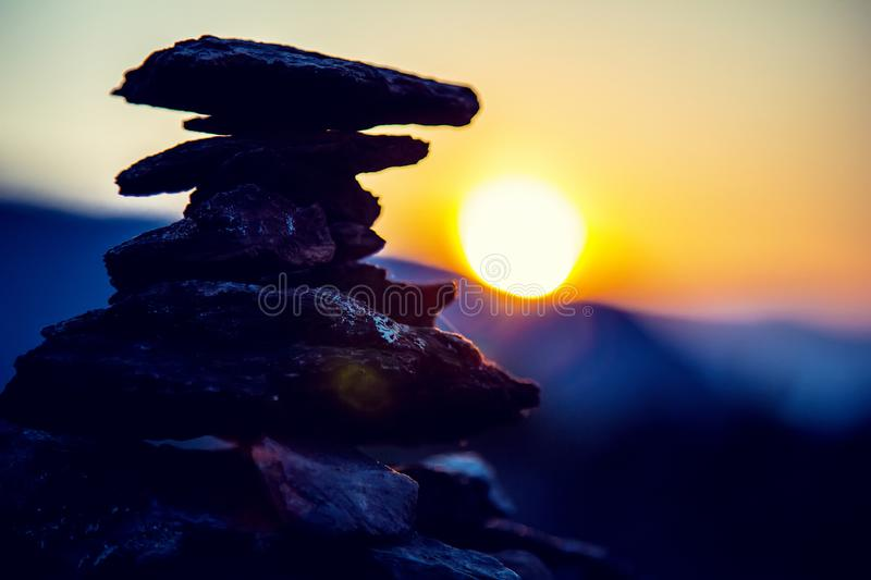 Spa stones balance, colorful summer sky background, silhouette of stacked pebbles and butterfly, beautiful nature royalty free stock photos