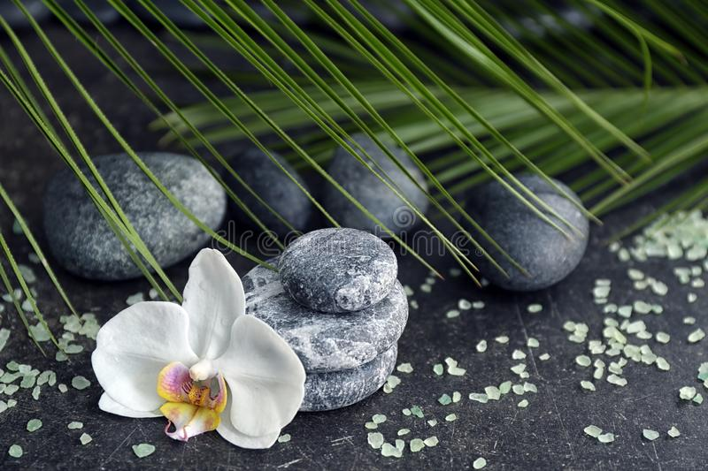 Spa stones and beautiful orchid flower on grey table royalty free stock images