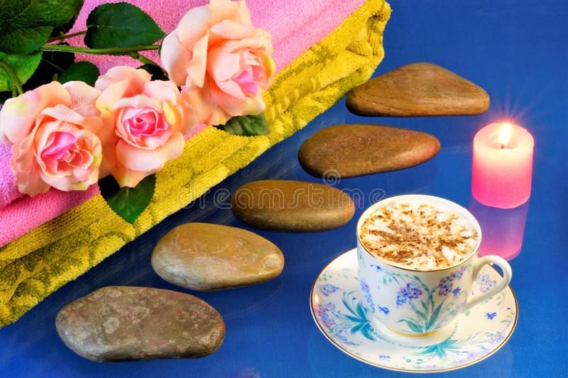 Spa stones, beautiful roses, candle and coffee. Hot stone massage-stone therapy, effective treatment for many diseases. On a blue stock photo