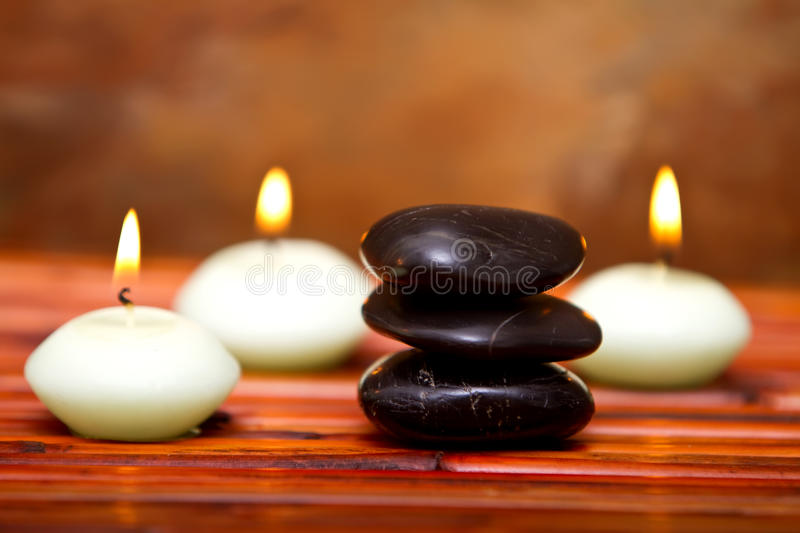 Spa stones and candles on bamboo royalty free stock photo