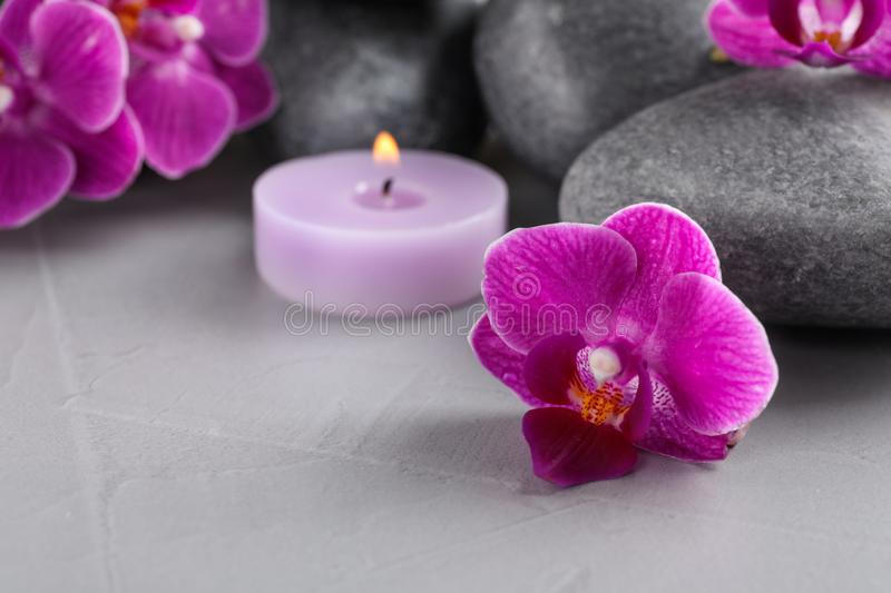Spa stones, orchid flowers and candle on  table, closeup. Spa stones, orchid flowers and candle on grey table, closeup royalty free stock photography