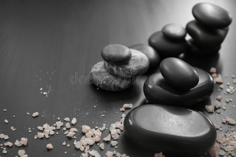 Spa stones and scattered sea salt on dark table stock photo