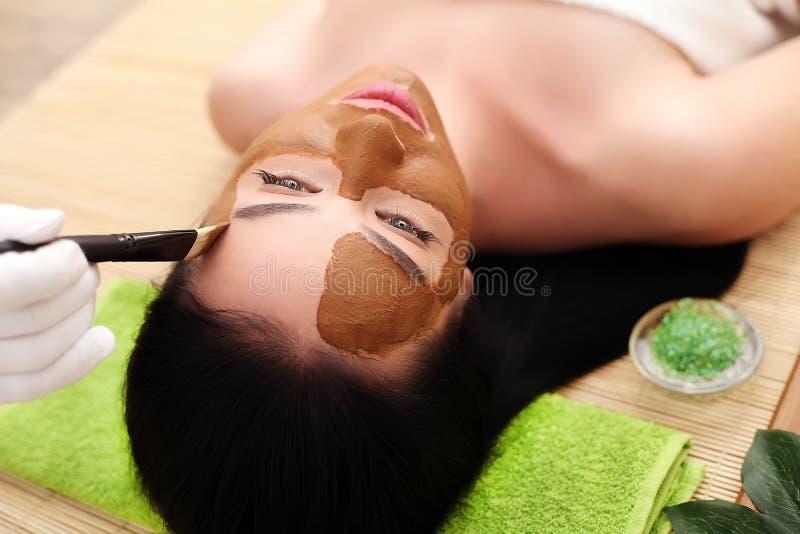 Spa terapi för den unga kvinnan som har den ansikts- maskeringen på skönhetsalongen - inomhus royaltyfria bilder