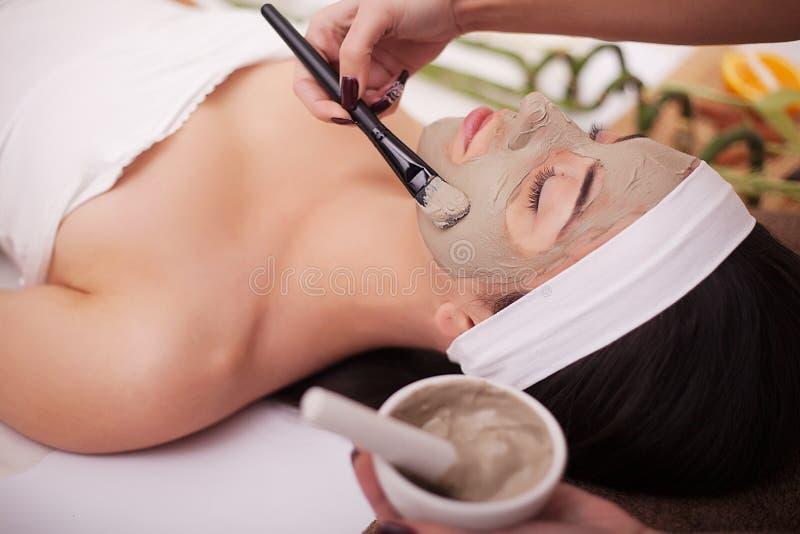 Spa terapi för den unga kvinnan som har den ansikts- maskeringen på skönhetsalongen - inomhus arkivfoton