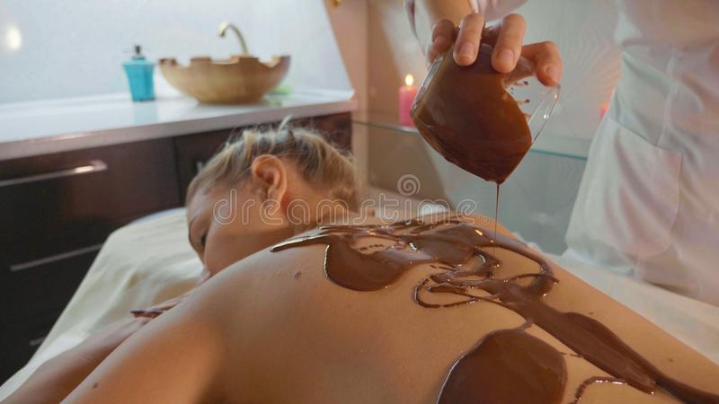 Spa therapist pouring hot chocolate on young woman back at luxury beauty salon royalty free stock photography