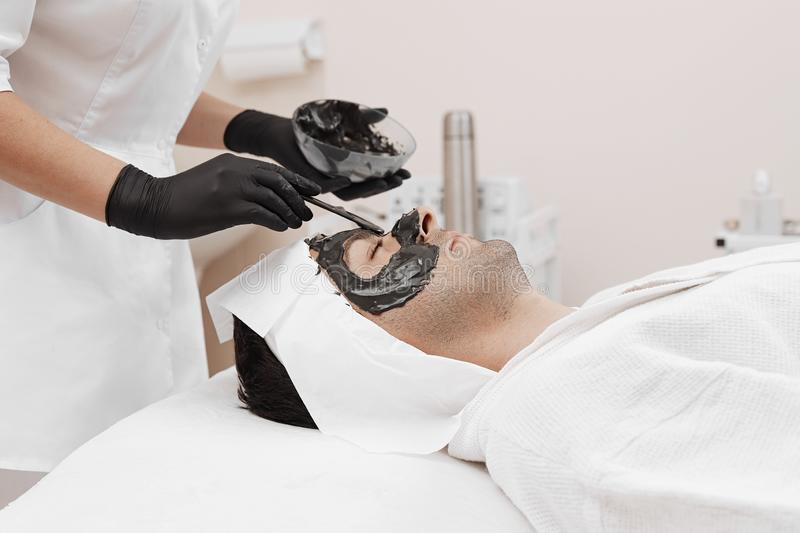 Spa therapy for men receiving facial black mask. Cleaning the face of a men in a beauty salon. Spa therapy for men receiving facial black mask royalty free stock image