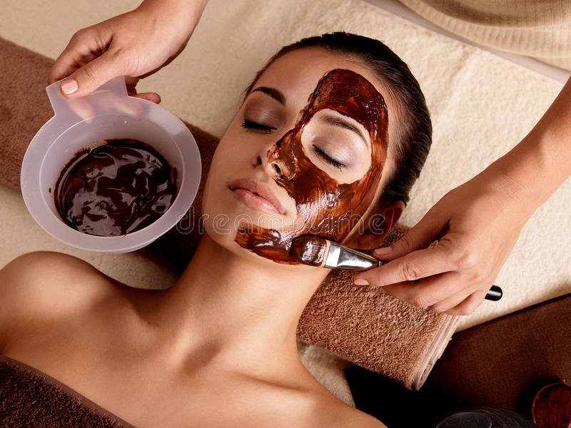 Spa therapy for woman receiving cosmetic mask stock photos