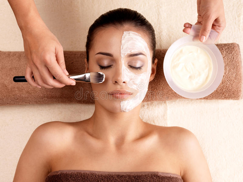 Spa therapy for woman receiving facial mask. Spa therapy for young woman receiving facial mask at beauty salon - indoors royalty free stock photo