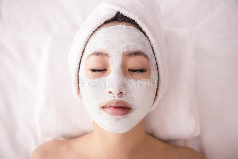 Spa therapy. For young asian woman receiving facial mask at beauty salon stock photo