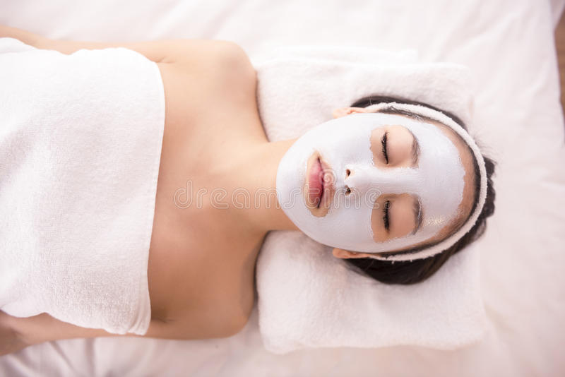 Spa therapy. For young asian woman receiving facial mask at beauty salon royalty free stock images