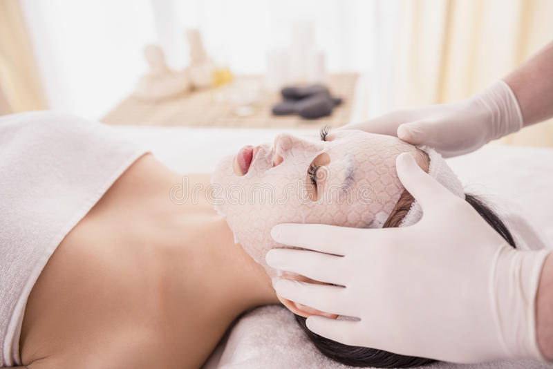 Spa therapy. For young asian woman receiving facial mask at beauty salon royalty free stock photos