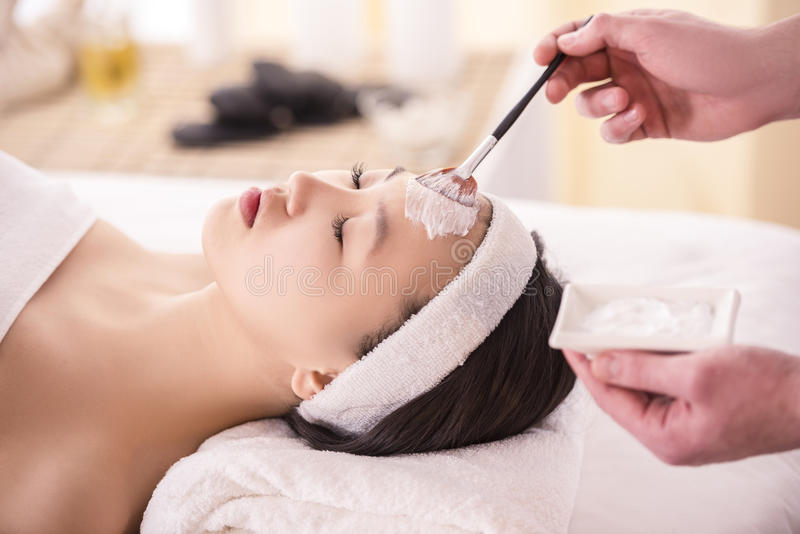 Spa therapy. For young asian woman receiving facial mask at beauty salon royalty free stock image