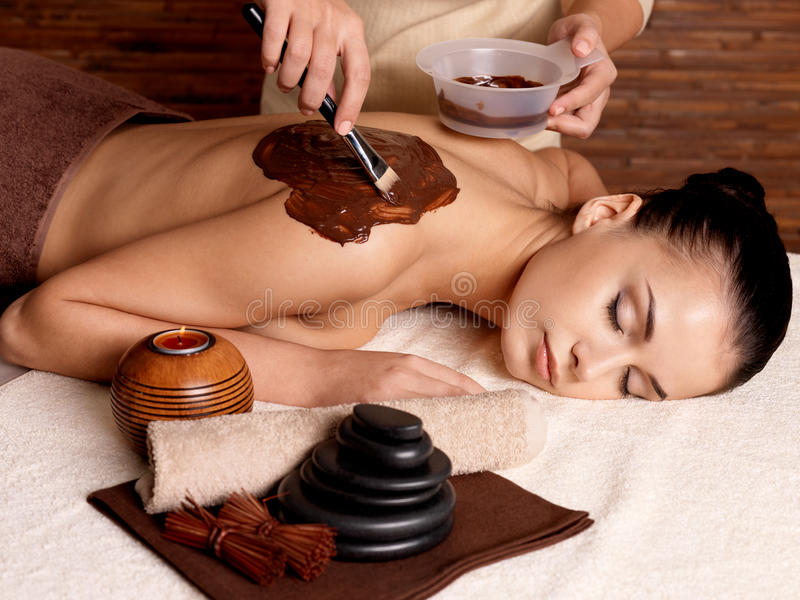 Spa therapy for young woman receiving cosmetic mask royalty free stock photography
