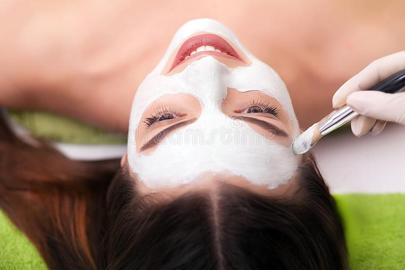 Spa therapy for young woman receiving facial mask at beauty salon - indoors royalty free stock image