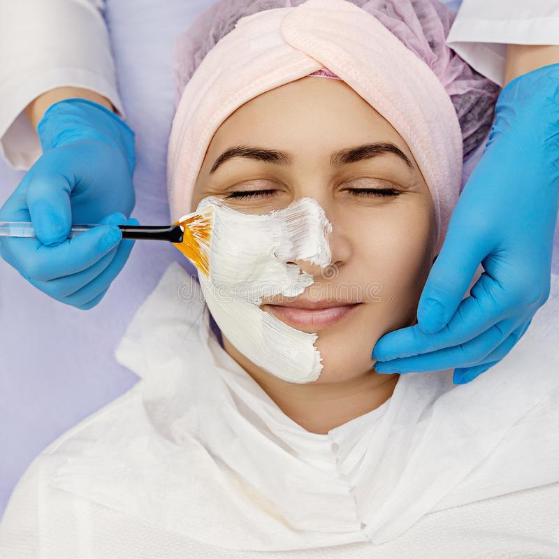 Spa therapy for young woman receiving facial mask at beauty salon. stock image