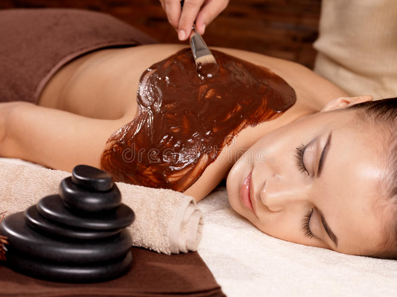 Spa therapy for young woman receiving mask stock photo