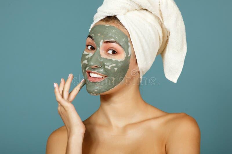 Spa tonårig flicka som applicerar den ansikts- leramaskeringen Skönhetbehandlingar arkivbilder