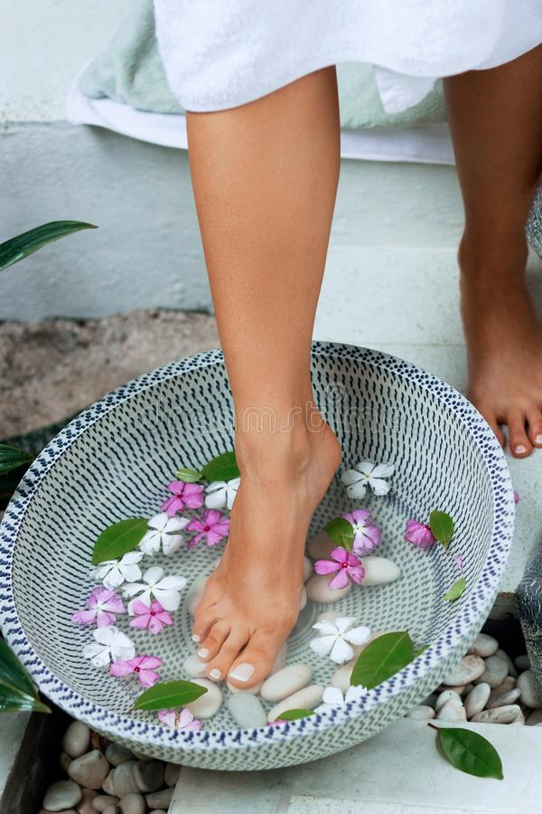 Spa treatment and product for woman feet and foot spa. Foot bath in bowl with tropical flowers, Thailand. Healthy Concept royalty free stock images