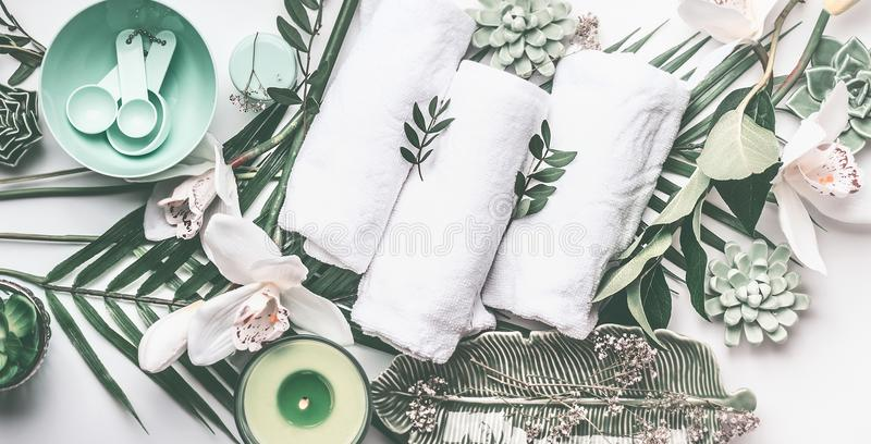 Spa treatment setting with towels, green candle, tropical leaves, white orchid flowers, top view. stock photo