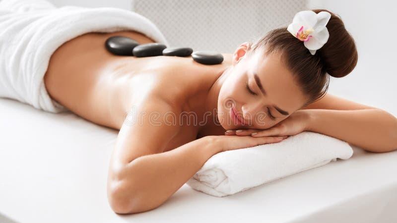 Spa treatment. Woman enjoying hot stone massage stock photo