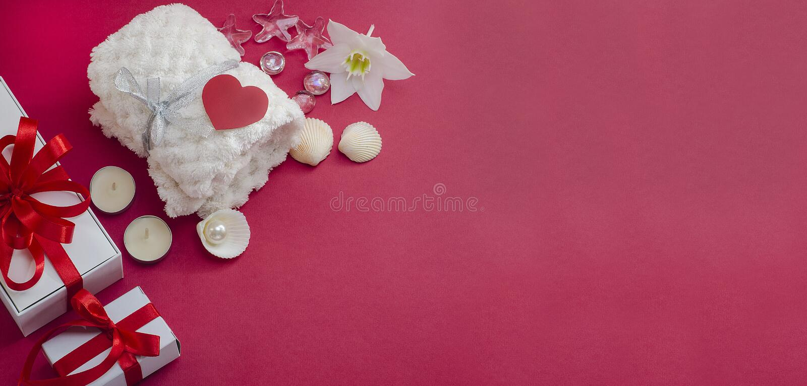 Spa treatments for Valentine`s Day. White towel with flower, shells and a pearl on a red background with a heart and gifts. Beaut. Spa treatments as a gift for stock photo