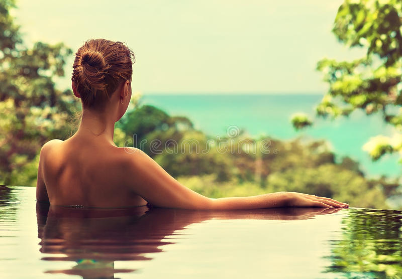 Spa treatments. Beautiful girl rests near the swimming pool , sunbathing. Spa treatments stock images
